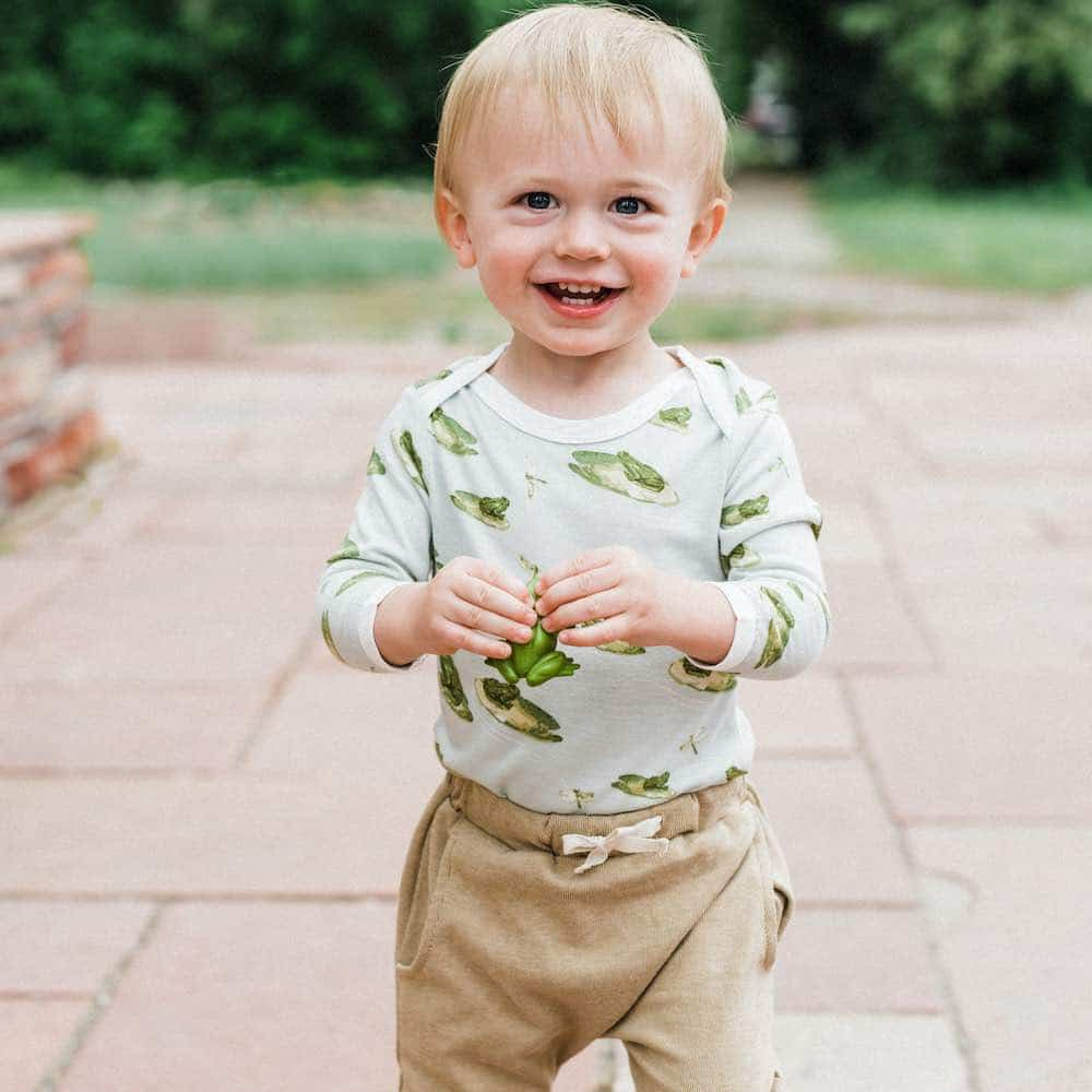 Little Baby Boy on a Patio Wearing the Bamboo Long Sleeve One Piece or Onesie in the Leapfrog Print and the Jogger Pant in the Rust Pinstripe by Milkbarn Kids