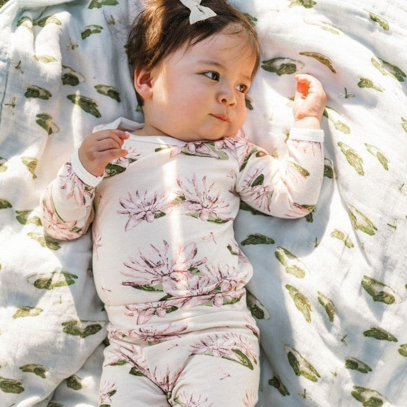 Little Girl on a Leapfrog Big Lovey Blanket Wearing a Bamboo Long Sleeve One Piece and Leggings in the Water Lily Print by Milkbarn Kids